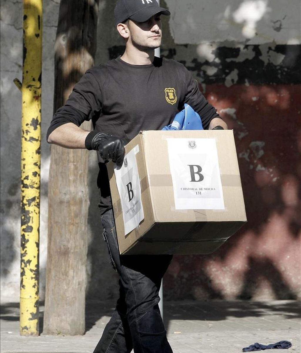 Un Mosso d'Esquadra transporta una caja con pruebas durante una macro operación policial que la policía autonómica catalana está llevando a cabo en el distrito de Sant Martí de Barcelona contra una banda dedicada al robo de cobre y a su comercialización, en la que han sido detenidas 50 personas. EFE