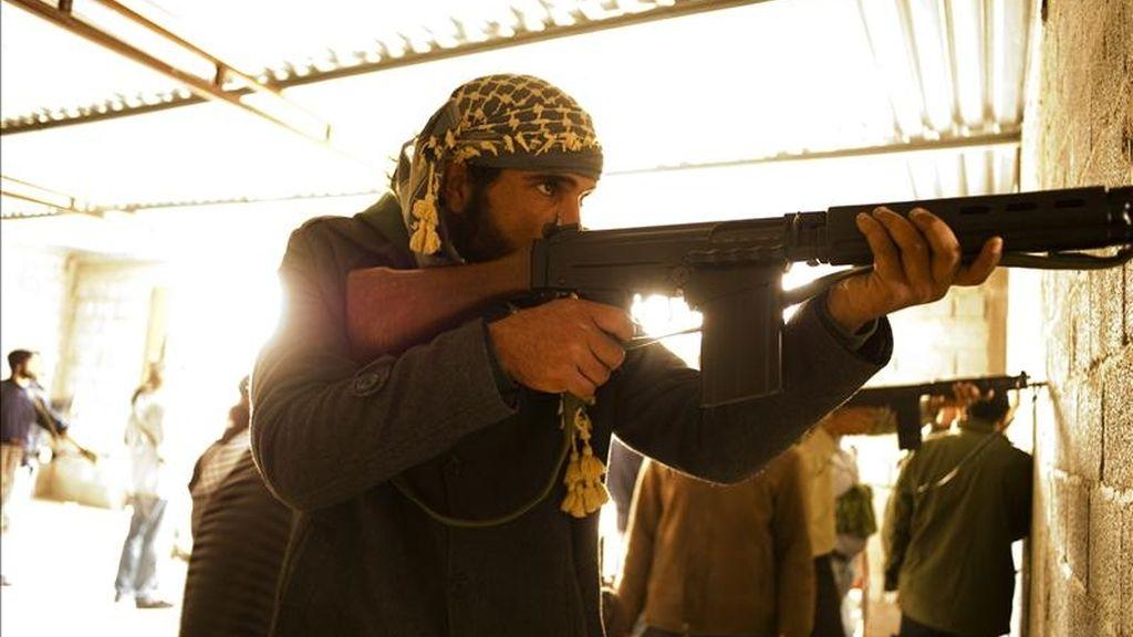 Un grupo de rebeldes opositores a Muamar el Gadafi participan en la toma de una casa utilizada como base por soldados progubernamentales el domingo 24 de abril de 2011, en Misrata (Libia). EFE