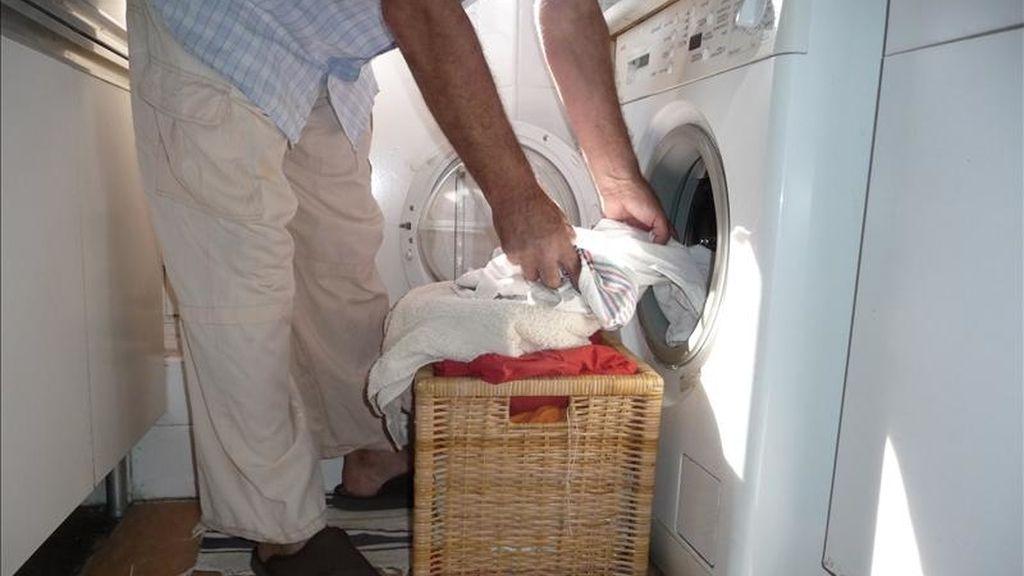 Un hombre introduce ropa en una lavadora doméstica. EFE/Archivo