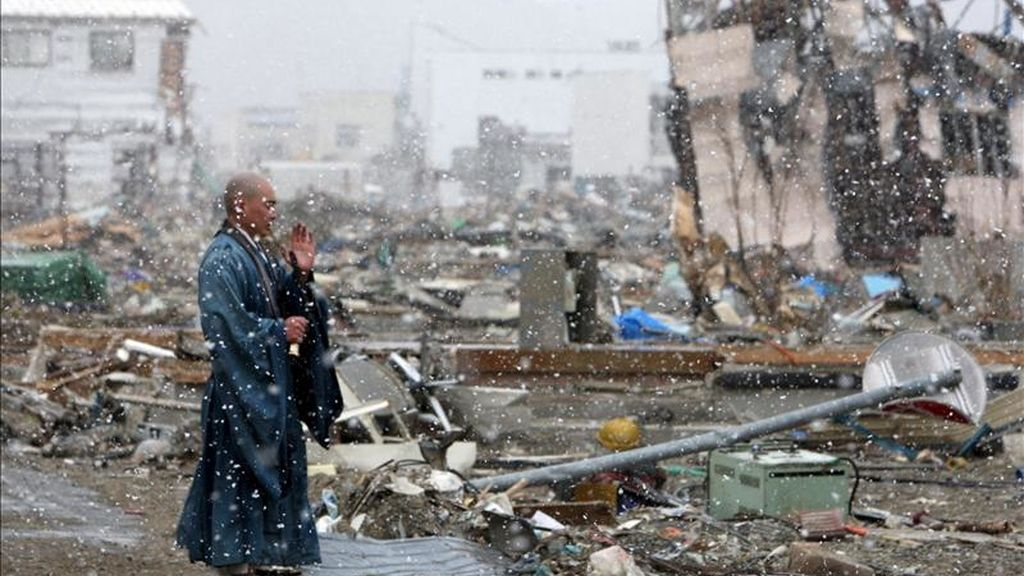 Un sacerdote budista japonés reza por las almas de las víctimas desaparecidas mientras nieva sobre la devastada ciudad de Yamada, en la prefectura de Iwate, hoy, lunes 4 de abril de 2011. EFE/Asahi Shimbun