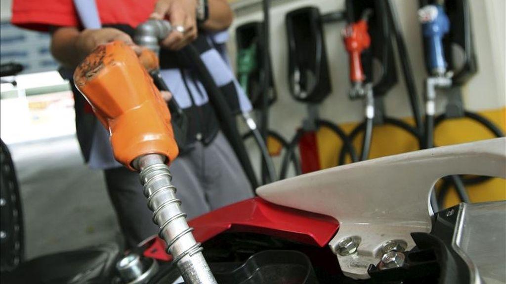 Un empleado llena el depósito de una moto en una gasolinera. EFE/Archivo