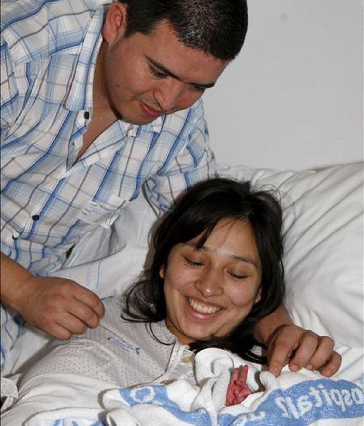 Una mujer de nacionalidad española y de origen colombiano de 24 años, junto a su pareja, observa a su pequeño Joel en una de las habitaciones del Hospital 12 de Octubre de Madrid, donde fueron trasladados ambos después de que la joven diera a luz esta madrugada en la vía pública, a la altura del número 115 de la calle General Ricardos. EFE