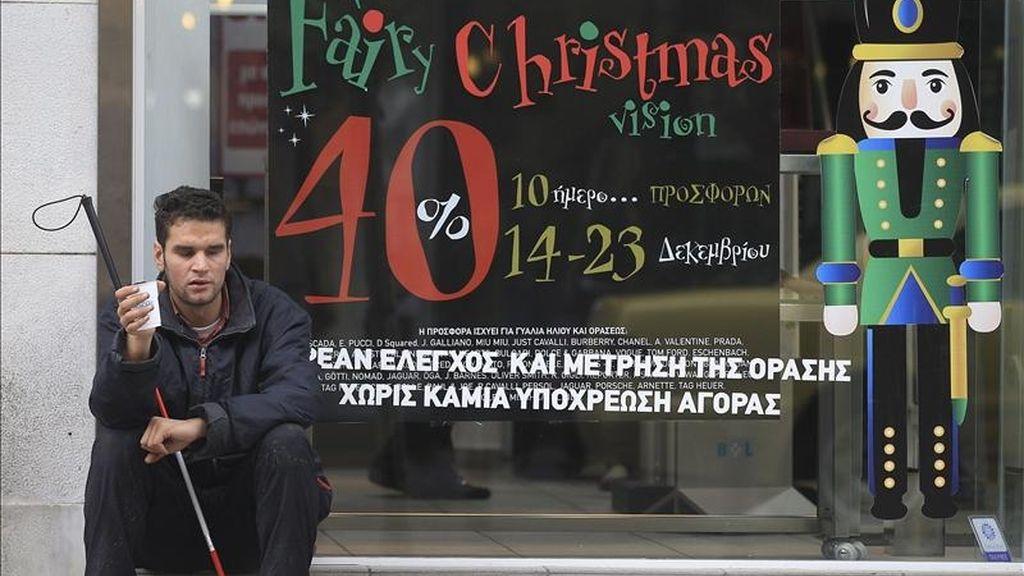 Un joven ciego pide limosna junto a una tienda en el centro de Atenas, Grecia. EFE/Archivo