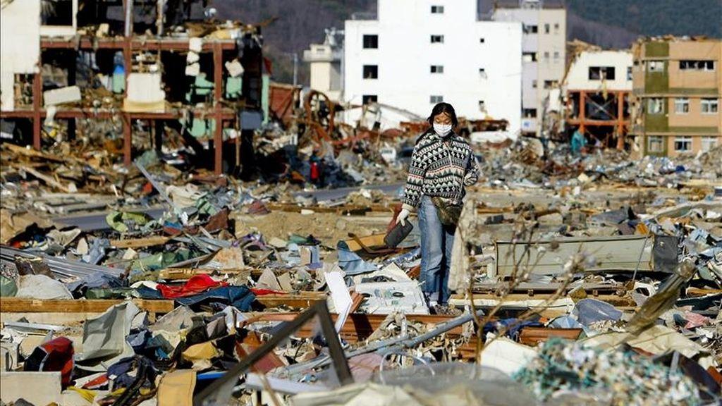 Una mujer camina por encima de una montaña de residuos producidos por el terremoto y el posterior tsunami de hace tres semanas en busca de objetos conocidos, en la ciudad de Onagawa, Japón. EFE
