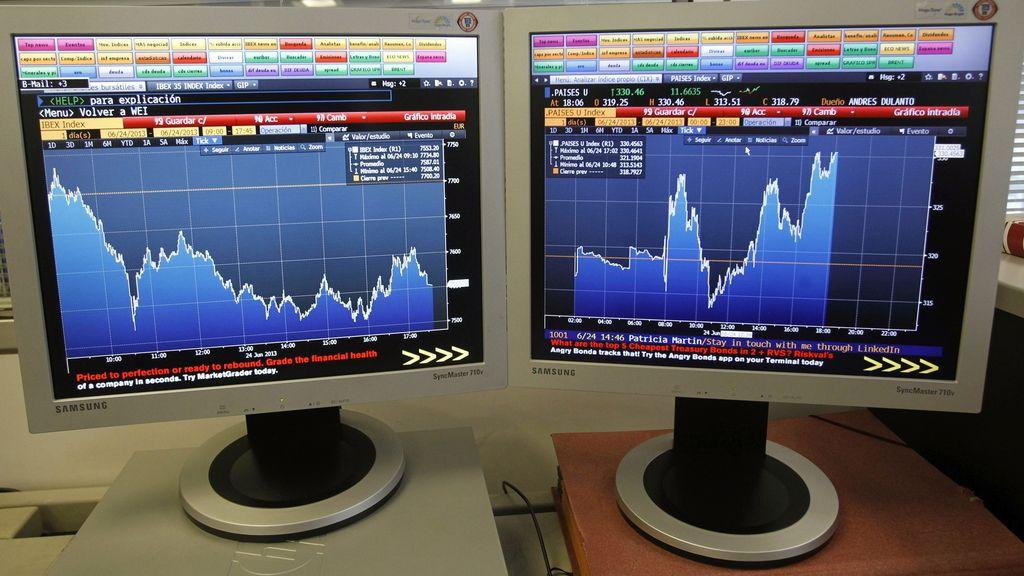 Pantallas que muestran la evolución hoy de la bolsa española (i) y la prima de riesgo