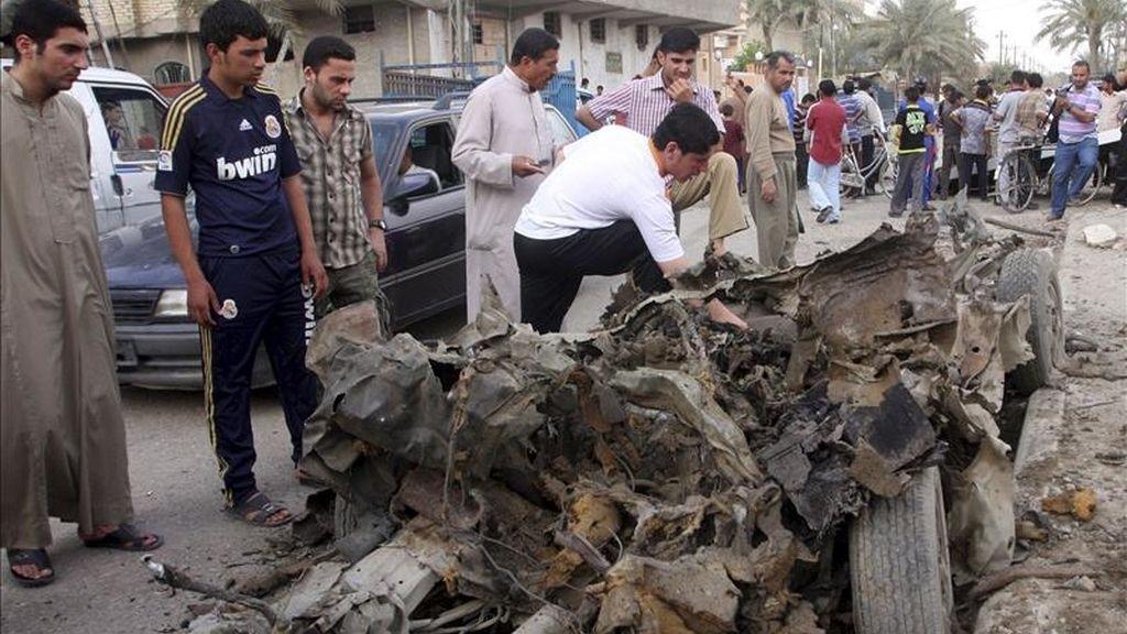 Iraquíes observan los restos de uno de los coche bomba que han hecho explosción en Faluya, Irak. EFE