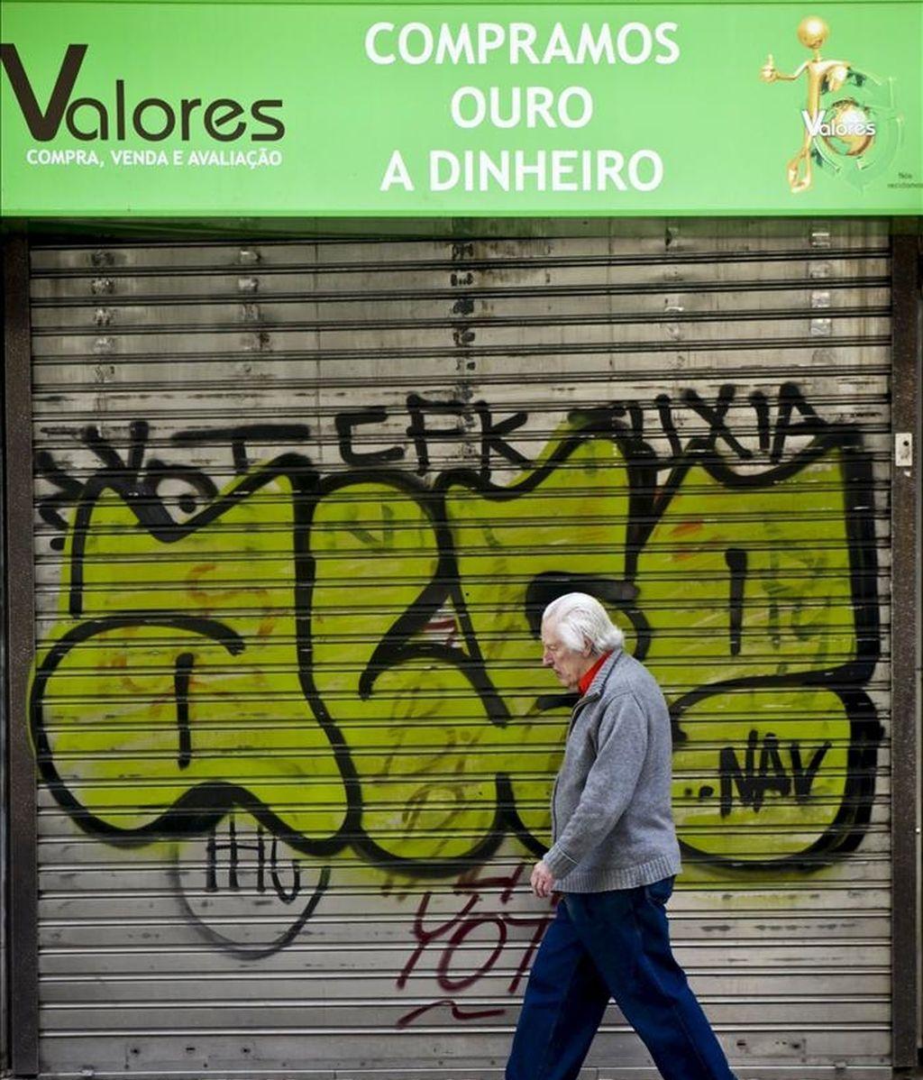 Un hombre pasa frente a un negocio cerrado de Lisboa, Portugal. EFE/Archivo