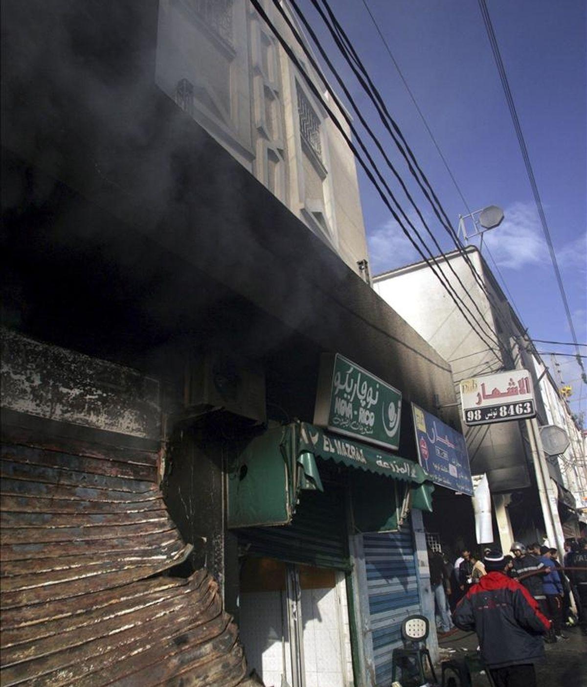 Vista de un centro comercial incendiado, donde los manifestantes quemaron vehículos y atacaron oficinas gubernamentales el martes, en el distrito de Ettadhamen, ubicada a varios kilómetros del centro de Túnez. EFE
