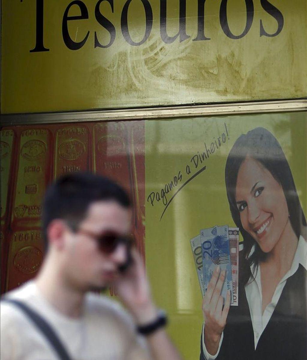Un hombre habla por teléfono mientras pasa delante de una tienda en la que se compra oro en Lisboa, Portugal. EFE/Archivo