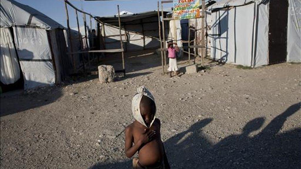 Un niño descansa mientras juega con otros en el campo de desplazados de Aviation, en Puerto Príncipe (Haití). Los haitianos conmemorarán el próximo 12 de enero el primer aniversario del terremoto de 7 grados que dejó más de 300.000 muertos y cambió la historia de este deprimido país. EFE/Archivo