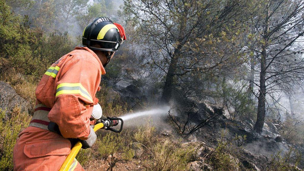 Un bombero combate el incendio que afecta al término municipal de Villalonga