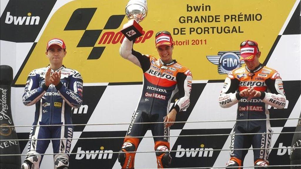 El piloto español de MotoGP de Repsol Honda, Dani Pedrosa (c), celebra en el podio la victoria conseguida en el Gran Premio de Portugal, junto al español de Yamaha, Jorge Lorenzo (izda), segundo, y al australiano de Repsol Honda, Casey Stoner, en el circuito de Estoril, el 1 de mayo de 2011. EFE