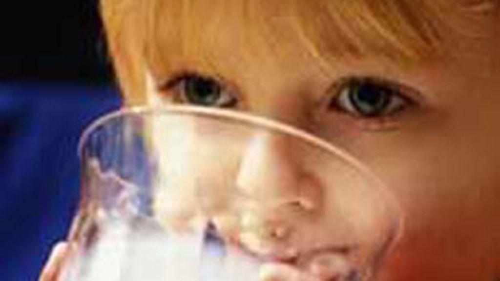 Niña bebiendo un vaso de leche. Foto: EFE