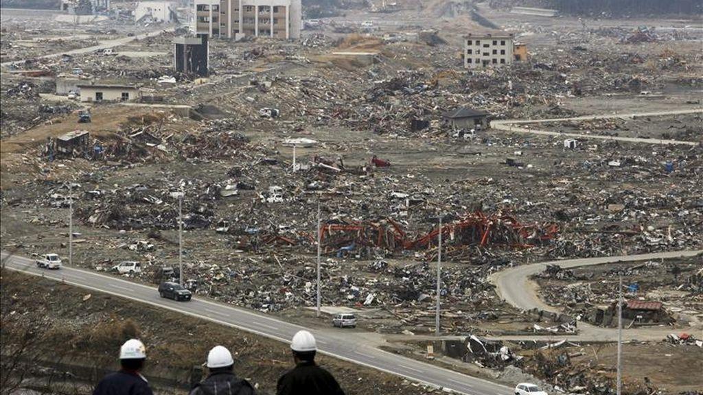 Operarios de la construcción observan desde una colina la ciudad costera de Minamisanriku, prefectua de Miyagi, totalmente devastada tras el paso de tsunami del 11 de marzo. El Gobierno y las empresas de Japón han comenzado a afinar los detalles de un plan de reconstrucción tras el seísmo, que podría necesitar más de 200.000 millones de euros y comenzará a tomar forma con un presupuesto de 33.000 millones. EFE