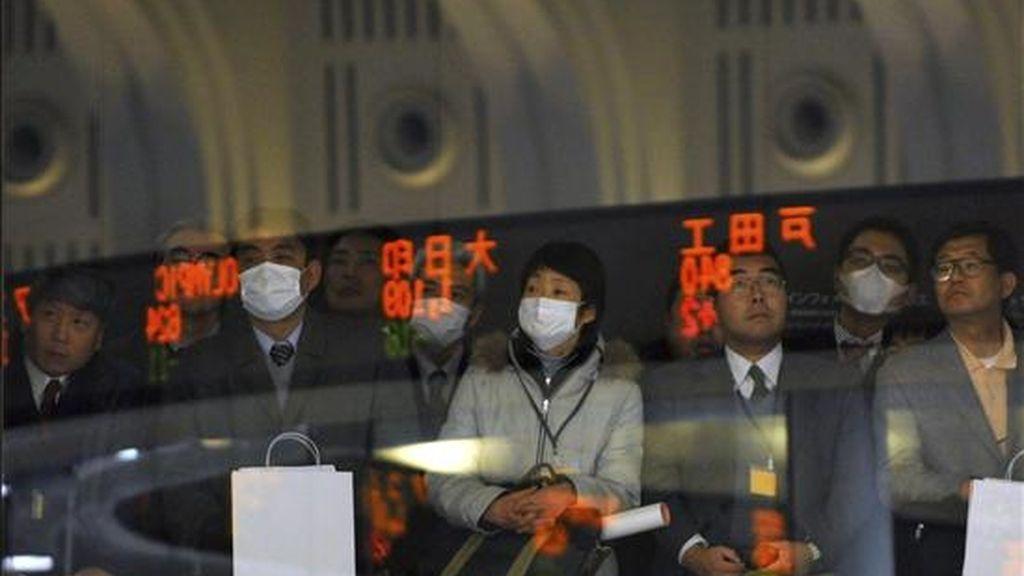 Los visitantes observan los indicadores electrónicos con las cifras de la Bolsa de Valores de Tokio. EFE/Archivo