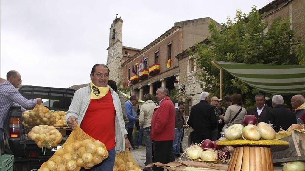 Un agricultor descarga sacos de cebollas en un mercado. EFE/Archivo