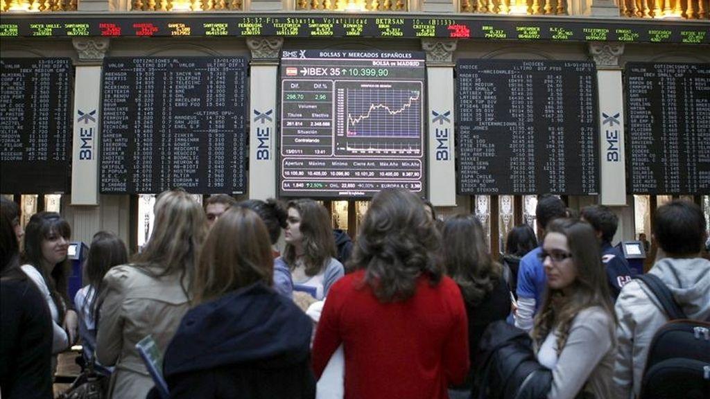 Un grupo de estudiantes de visita hoy en la bolsa de Madrid, ante el panel del IBEX 35. EFE
