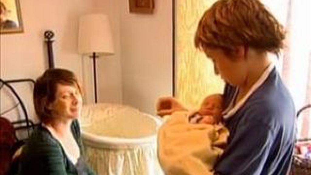 El niño de 12 años con su hermano en brazos, junto a su madre, a la que acudió en el parto. Imagen CTV vídeo