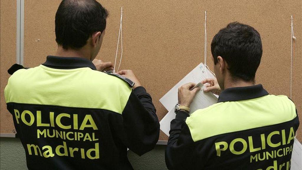 Un agente de la Policía Municpal de Madrid cuelga los listados con el censo electoral en un colegio público. EFE/Archivo