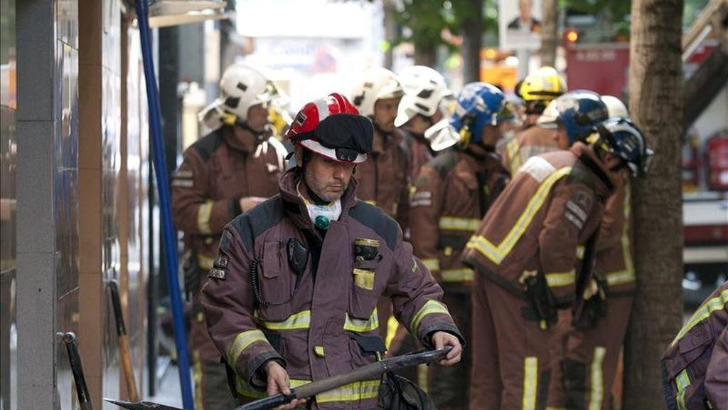 Efectivos de los bomberos y de otros equipos de emergencias trabajan en los escombros de un edificio derrumbado hoy en Santa Coloma de Gramenet (Barcelona). EFE