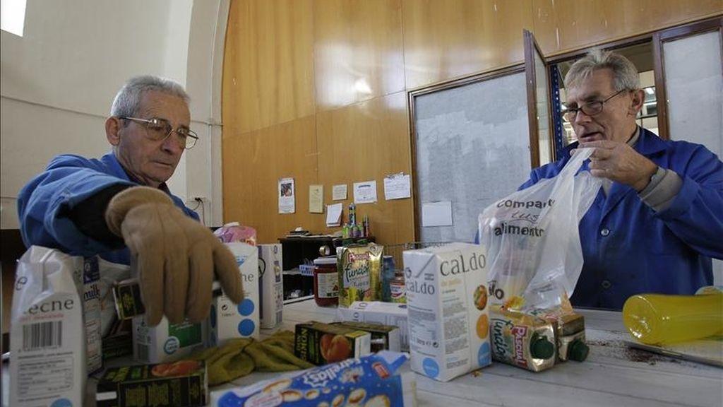 En la imagen dos voluntarios introducen alimentos de un banco de alimetación en bolsas para su posterior distribución. EFE/Archivo