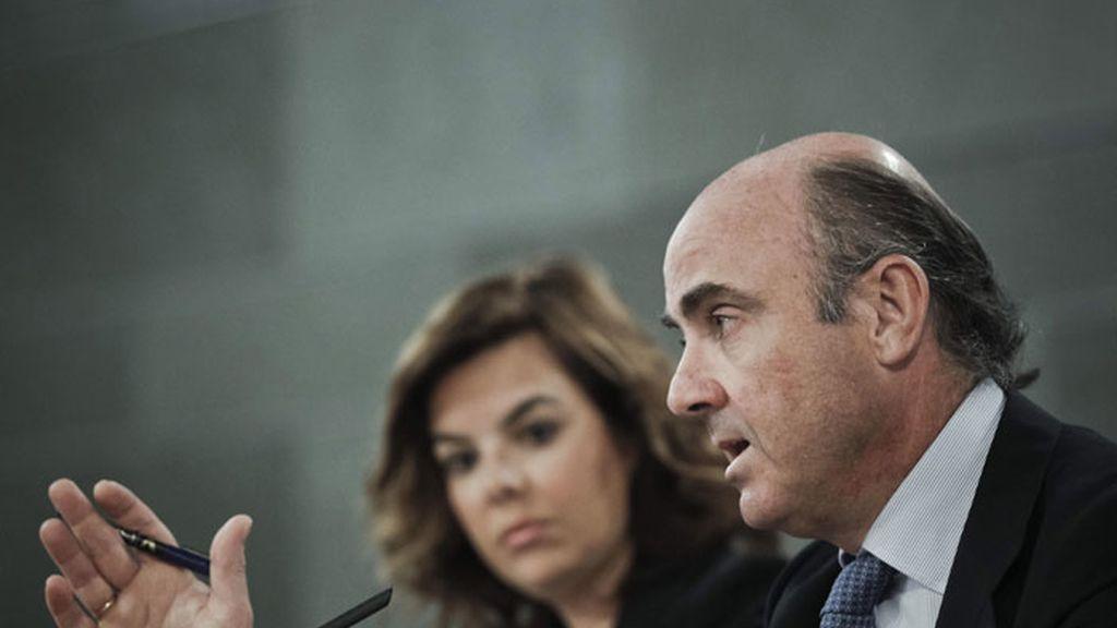 El titular de Economía, Luis de Guindos, durante la rueda de prensa junto a la vicepresidenta del Gobierno, Soraya Sáenz de Santamaría