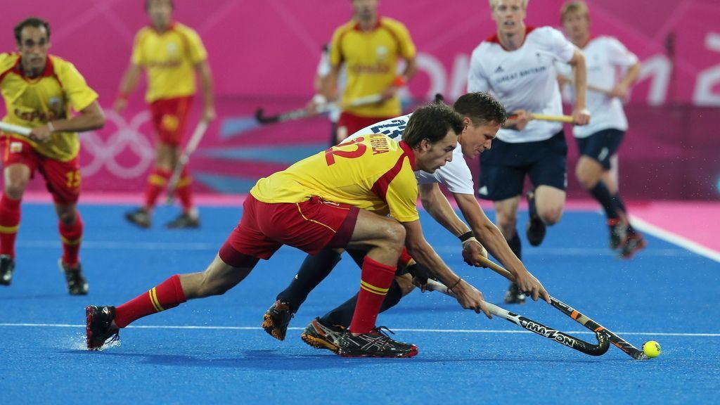 El español Manel Terraza (c) domina la bola ante la marca del británico Iain Mackay durante el partido de la ronda preliminar de hockey sobre hierba de los Juegos Olímpicos Londres 2012