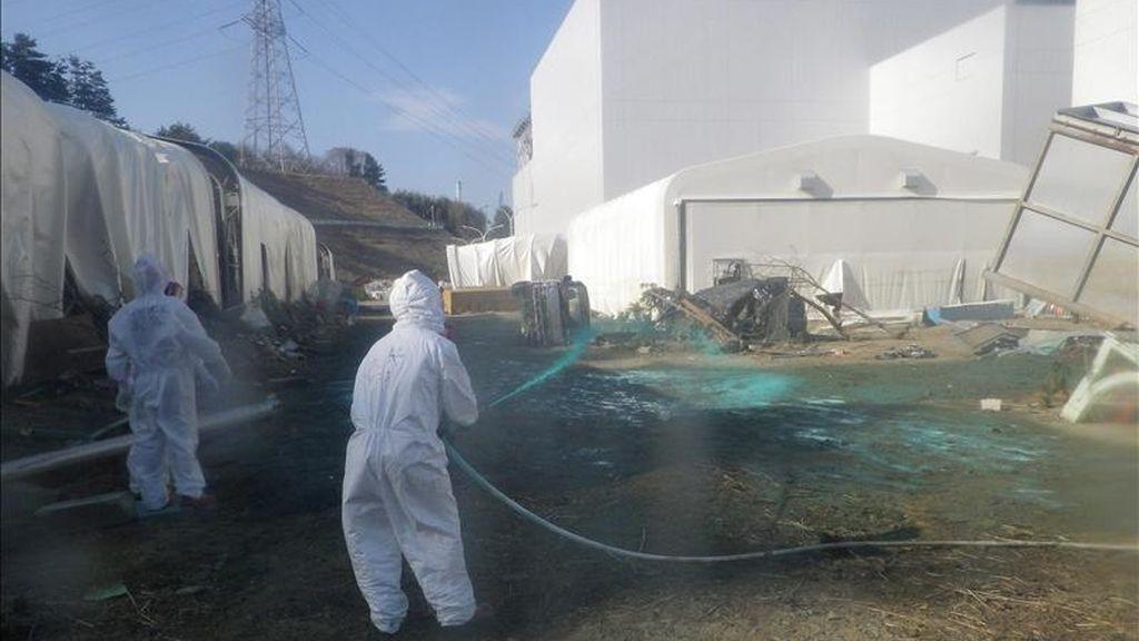 Tabajadores riegan con resina verde a base de polvo protector en el área de una piscina dañada en la planta nuclear de Fukushima Daiichi, al noreste de Japón. EFE/TEPCO