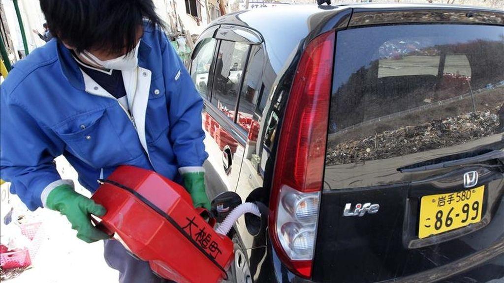 Un trabajador llena el tanque de un vehículo con una de las raciones de 20 litros de combustible, hoy en la ciudad costera devastada por el tsunami, de Otsuchi, en la prefectura de Iwate, noreste de Japón. EFE