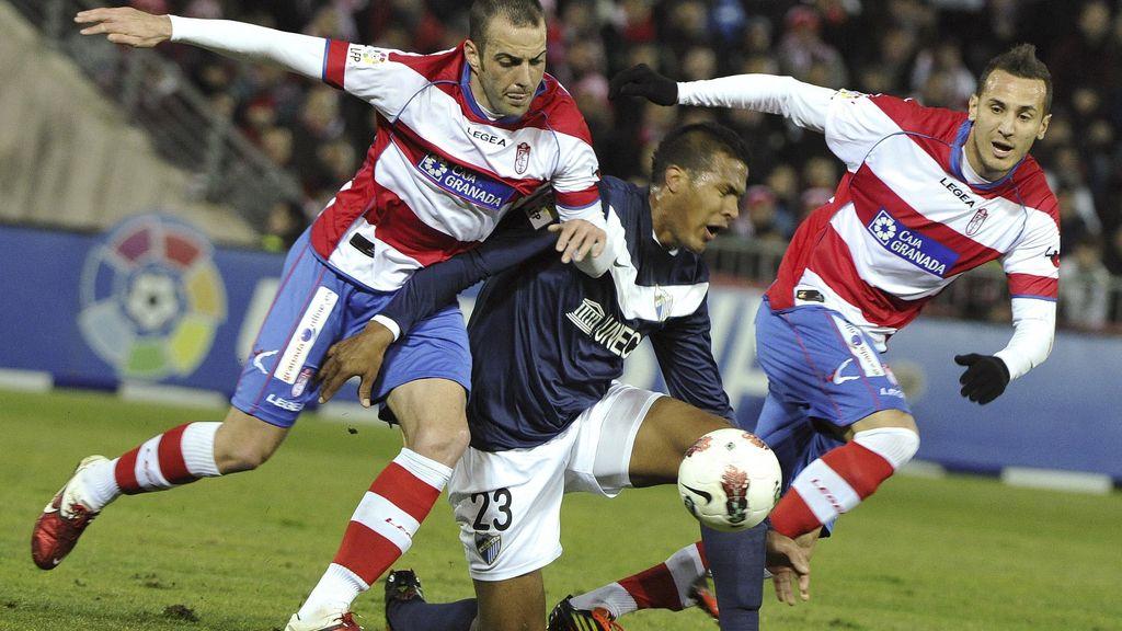 El delantero venezolano del Málaga, José Rondón, pelea un balón ante los jugadores del Granada, Borja Gómez y el argelino Hassan Yebda