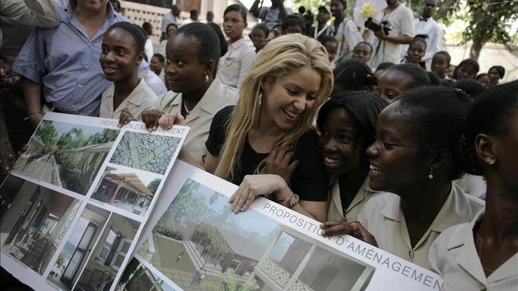 La cantautora colombiana Shakira (ci) posa con algunas estudiantes e imágenes de la futura sede de la escuela Elie Dubois el 31 de marzo de 2011, en el centro de Puerto Príncipe. El BID y la Fundación Pies Descalzos de la artista colombiana, donaron 566.000 euros para la reconstrucción de la histórica escuela. EFE