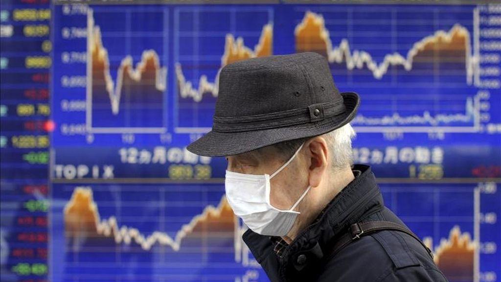 Un ciudadano pasa delante de una pantalla que muestra información bursátil en Tokio (Japón). EFE