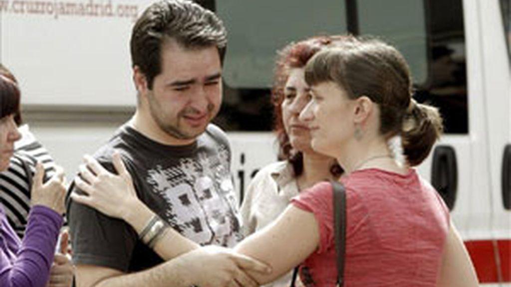 Varias personas junto al compañero de la mujer de 34 años trabajadora en una Administración de Loterías de la calle Juan XXIII de Móstoles (Madrid), que ha fallecido hoy tras recibir varias puñaladas por un individuo que ha asaltado el local y que ha huido tras cometer la agresión. EFE