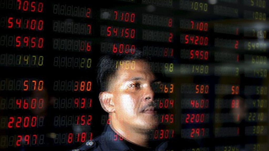 Un hombre reflejado en una pantalla que muetra la evolución de varios valores burstátiles en Yakarta (Indonesia). EFE/Archivo