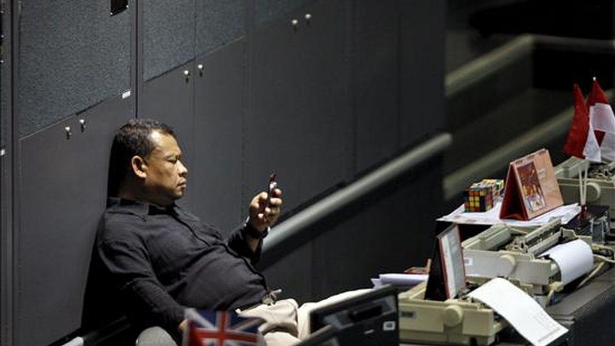 Un inversor indonesio observa su teléfono móvil en la Bolsa de Yakarta, Indonesia. EFE/Archivo