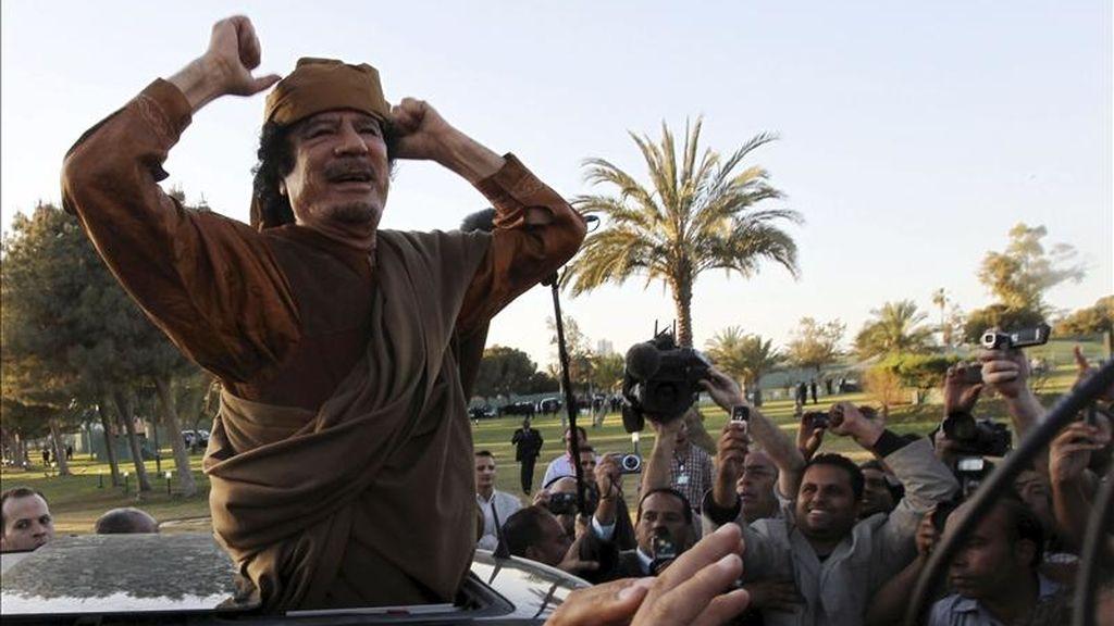 El líder libio Muamar el Gadafi saluda desde un vehículo en el complejo de gobierno de Bab el Azizia, donde Gadafi tiene su residencia oficial, tras una reunión con una delegación de cinco líderes africanos que buscan mediar en el conflicto de Libia, en Trípoli, Libia, el pasado 10 de abril. EFE/Archivo