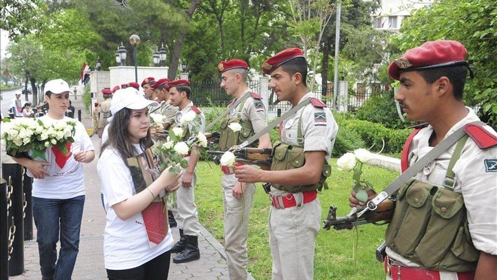 Imagen facilitada por la agencia siria de noticias Sana que muestra a jóvenes sirias ofreciendo flores a soldados sirios, en Damasco, Siria. EFE