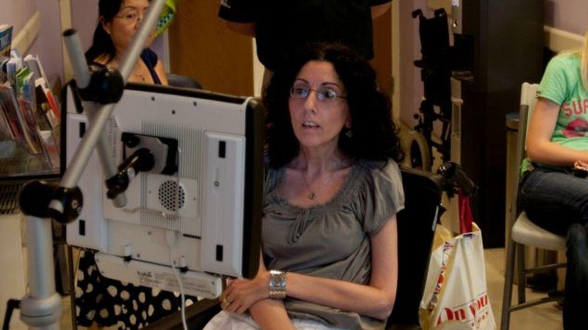 Una mujer con parálisis cerebral expone cuadros pintados con los ojos