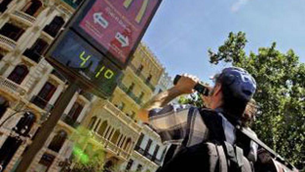 Un joven toma una fotografía de un termometro. Foto: EFE