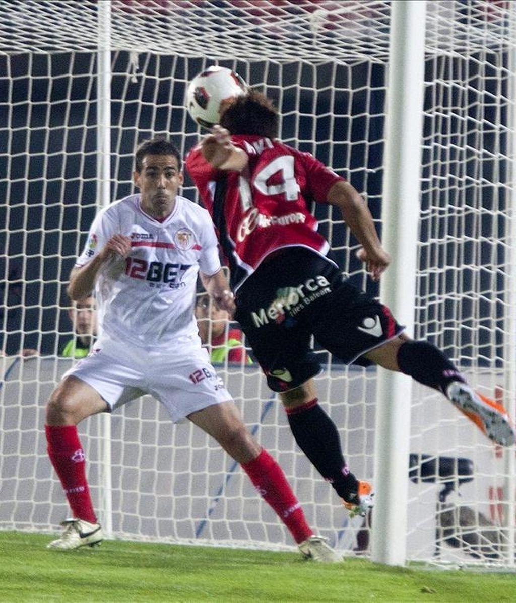 El centrocampista japonés del RCD Mallorca Akihiro Ienaga (d) remata un balón ante el defensa del Sevilla CF Fernando Navarro durante el partido correspondiente a la trigésimo primera jornada del Campeonato Nacional de Liga de Primera División que enfrentó a ambos equipos en el estadio Iberostar. EFE