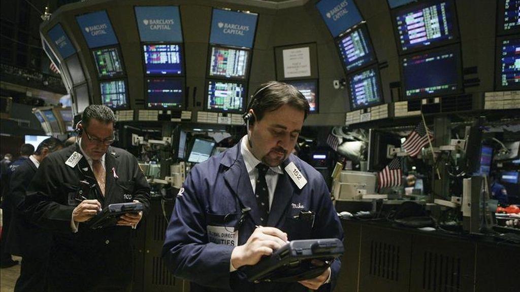 Al cierre de la jornada, el índice Dow Jones de Industriales, que agrupa a 30 de las mayores empresas cotizadas en este país, restó 30,88 puntos para acabar en 12.319,73. En la imagen un corredor fue registrado durante la sesión de este jueves en Wall Street. EFE