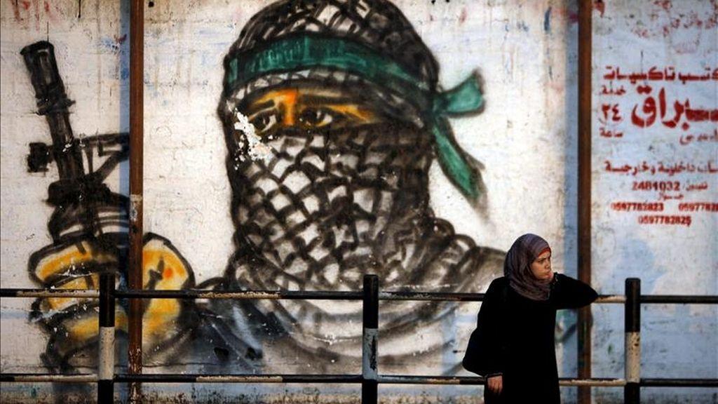 Una palestina espera frente a un mural, en el campo de refugiados de Jabaliya, al norte de la Franja de Gaza. EFE