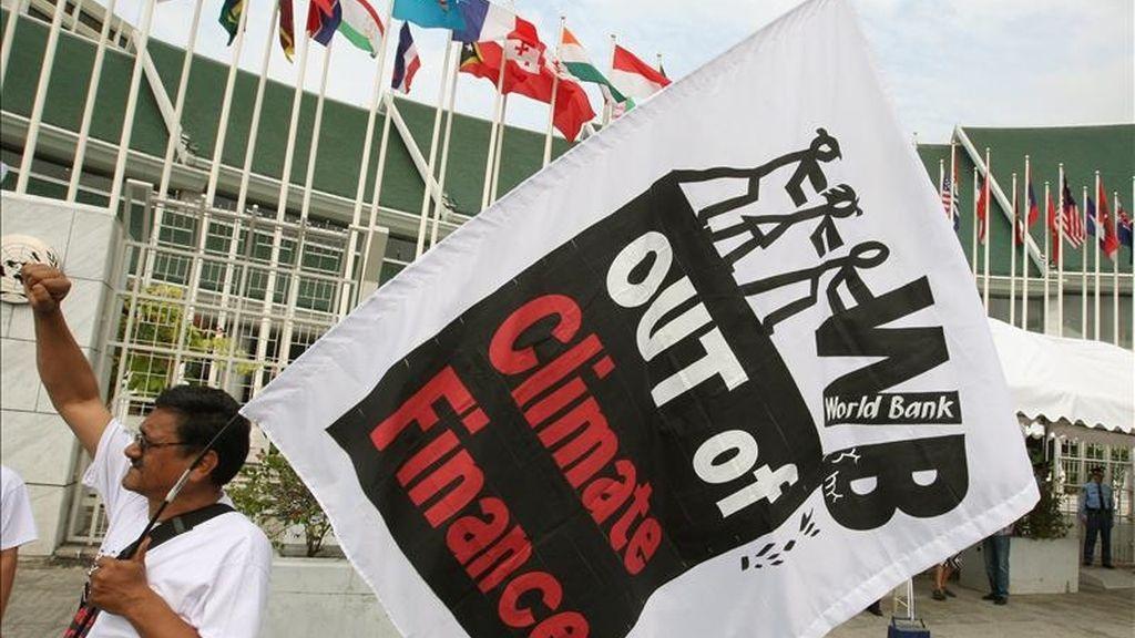 """Activistas sostienen banderas con un eslogan que dice """"Fuera el Banco Mundial de la Financiación Climática"""" durante una manifestación hoy, frente al Centro de la Conferencia de Naciones Unidas en Bangkok (Tailandia). EFE"""