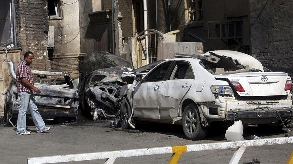 Un hombre iraquí observa los restos carbonizados de unos coches alcanzados por dos cohetes frente al hotel Ambassador en la calle Abu Nawas del centro de Bagdad. EFE/Archivo