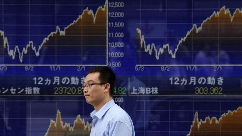 Un hombre camina frente a una pantalla con los indicadores de la bolsa en Tokio (Japón). EFE/Archivo