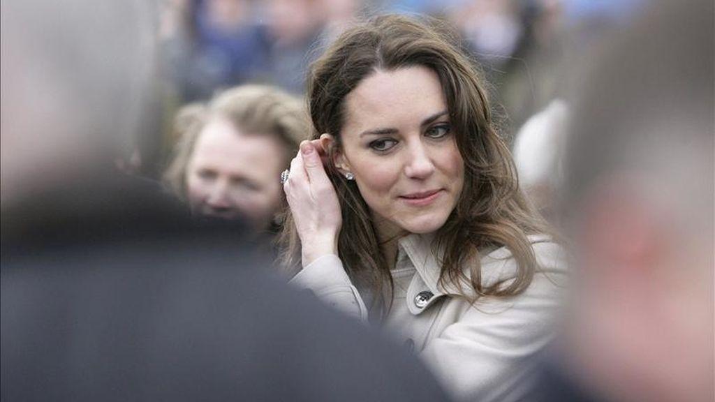 La futura esposa del príncipe Guillermo de Inglaterra, Kate Middleton, se coloca un mechón de pelo detrás de la oreja durante su visita junto a su prometido (no aparece en la imagen) al College of Agriculture, Food and Rural Enterprise, cerca de Antrim (Irlanda del Norte), Reino Unido, el 8 de marzo de 2011. EFE/Archivo