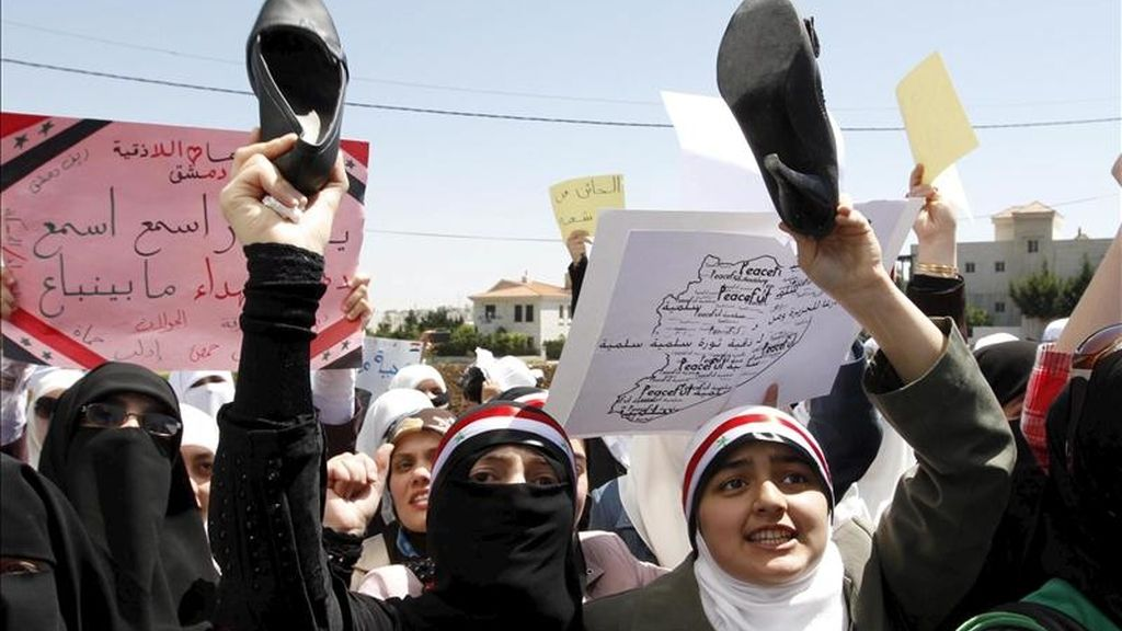 Manifestantes sirios residentes en Jordania sostienen sus zapatos y gritan consignas en contra del presidente de Siria, Bashar al-Assad, durante una manifestación frente a la embajada siria en Ammán, Jordania, el domingo, 24 de abril. EFE