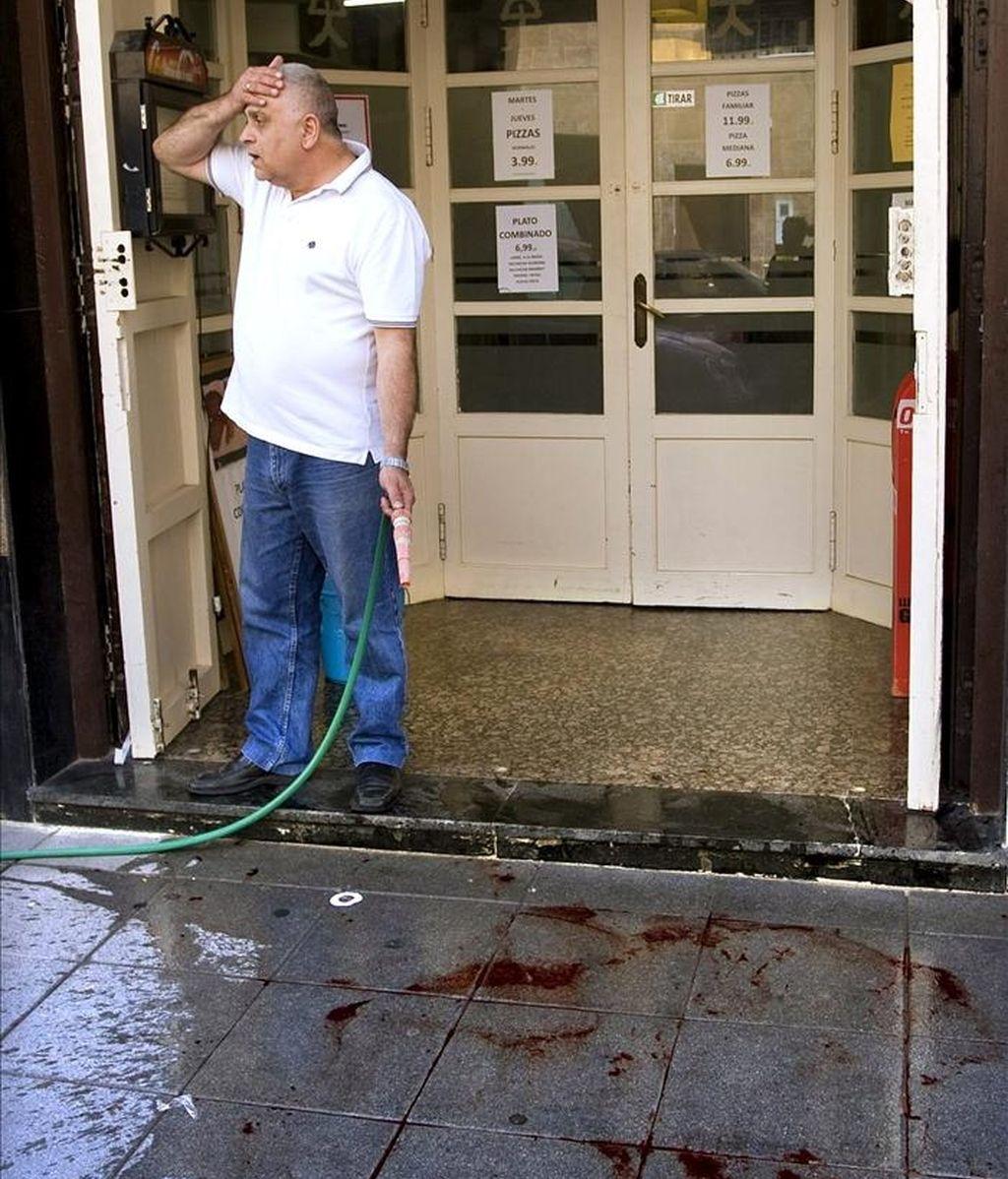 Un hombre limpia restos de sangre ante su establecimiento, en el lugar en el que murió apuñalada, presuntamente, por su pareja en Almería. EFE
