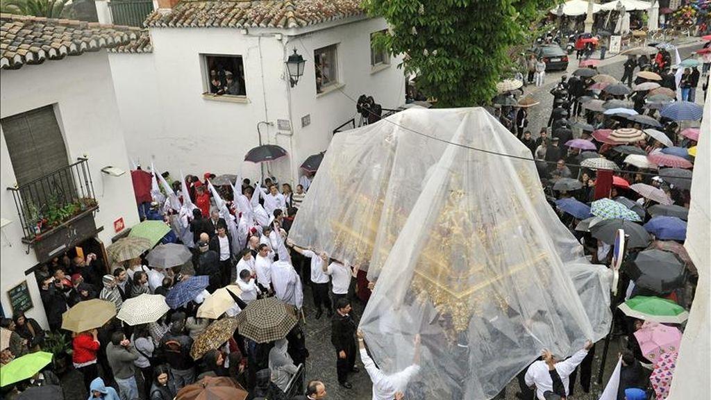 El paso de la Cofradía de Nuestro Padre Jesús del Perdón y María Santísima de la Aurora protegido con un plástico realiza su recorrido procesional hoy, Jueves Santo, en el barrio del Albaicín de Granada. EFE