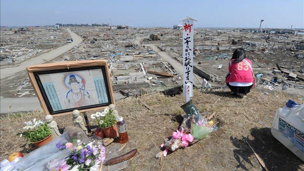 Residentes locales oran en un monumento budista hoy, 10 de abril de 2011, junto a los escombros de la devastación producida por el tsunami que destruyó a Natori (Japón). Japón vota en elecciones locales condicionadas por el devastador terremoto. EFE